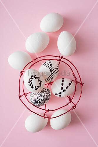 Mit schwarzem Stift bemalte Eier im selbstgemachten Drahtkörbchen