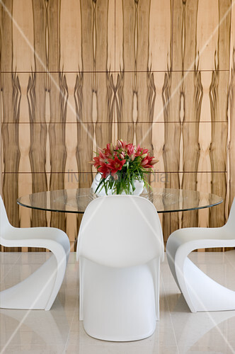 White designer chairs around glass table in front of wood-clad wall