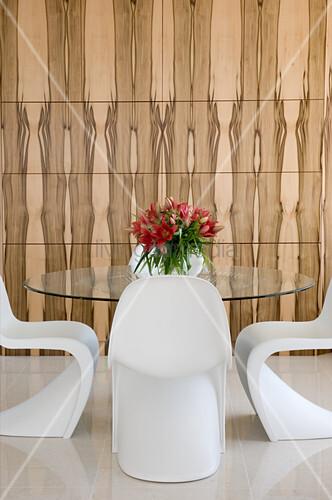 weiße Designerstühle um Glastisch vor Holzverkleidung