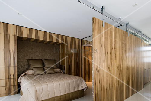 Elegant double bed in sleeping area screened by sliding wooden elements