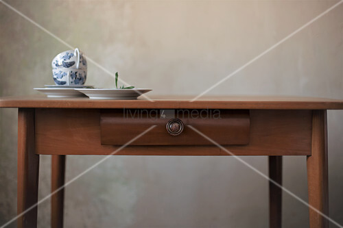 Teacups on wooden table with drawer