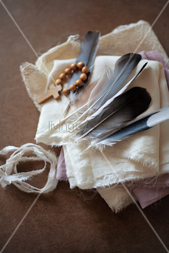 Feathers and cross on wooden beads on white cloth