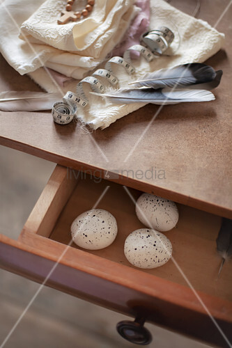 White cloth and feathers on table and speckled eggs in open drawer