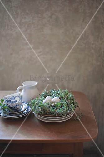 Frühstücksgeschirr und besprenkelte Eier im Osternest