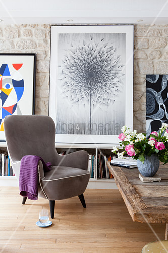 Grey armchair in front of picture of dandelion clock in living room