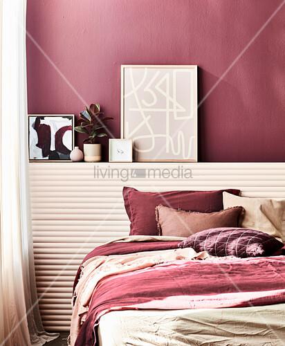 Doppelbett vor Wandvorsprung mit Dekoobjekten im Schlafzimmer, dunkelrote Wand und farblich passende Accessoires