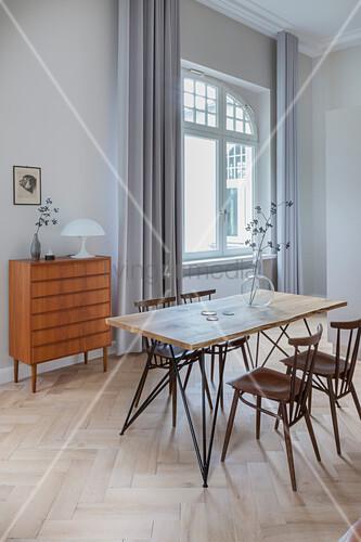Esstisch mit Holzplatte und Stühle vor Kommode in Altbauwohnung
