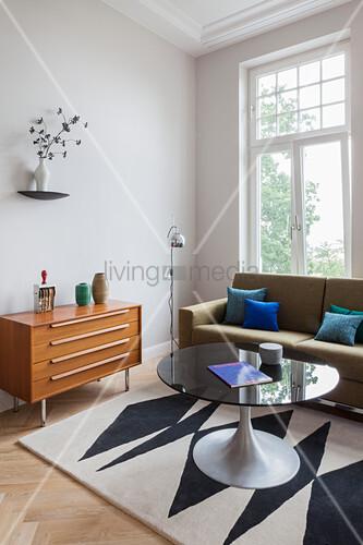 Sofa, runder Couchtisch auf Teppich und Sideboard in Altbauwohnung