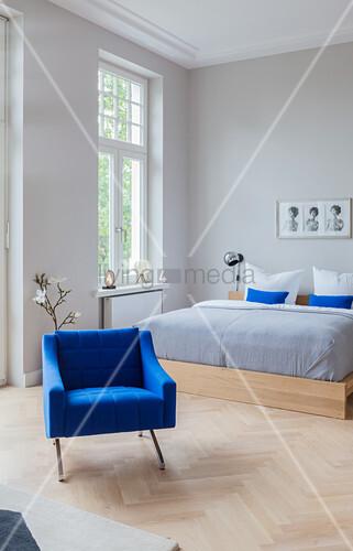 Blauer Polstersessel vor Doppelbett im Altbau-Schlafzimmer