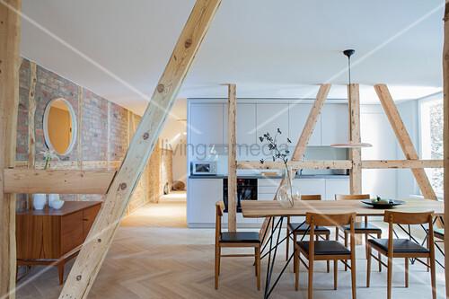 Essbereich und schlichte Einbauküche, getrennt durch Holzstützen