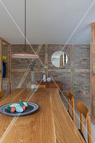 Dining area in front of brick wall in open-plan interior