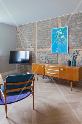 TV and sideboard in living room with brick wall