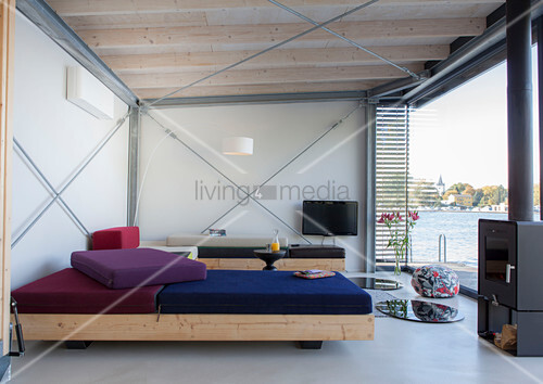 Modern houseboat: custom sofas, log burner and TV in living area