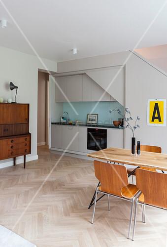 Schlichte Einbauküche, Highboard und Essbereich in offenem Wohnraum