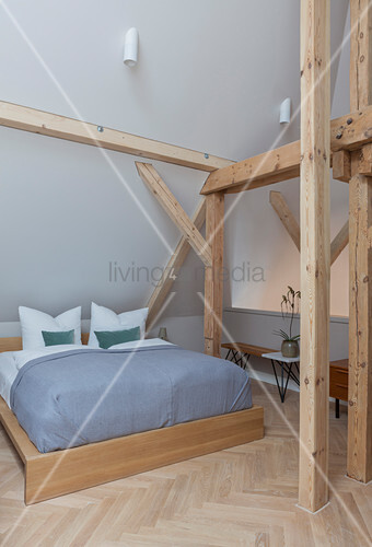 Wooden double bed in bedroom of period apartment with wooden beams