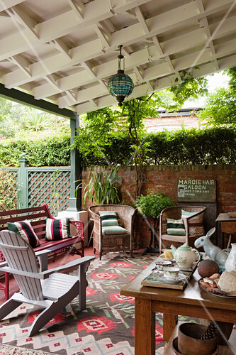 Eclectically furnished veranda with rug and lantern