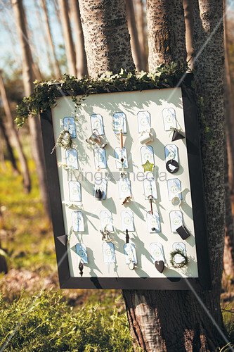 Labels with knick-knacks in picture frame hung on tree