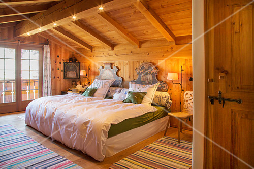 Double bed in attic bedroom in traditional Swiss farmhouse
