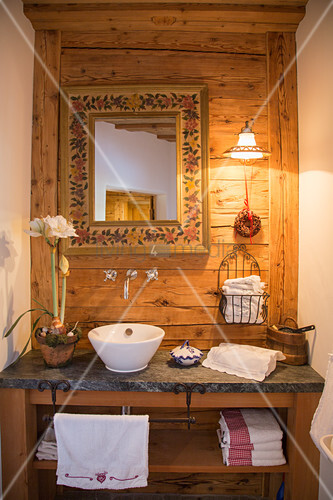 Washstand with mirror on wooden wall in farmhouse
