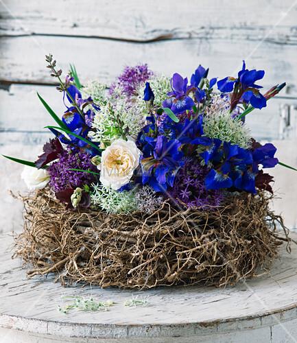 Iris, Rosen und Zierlauch im Nest arrangiert