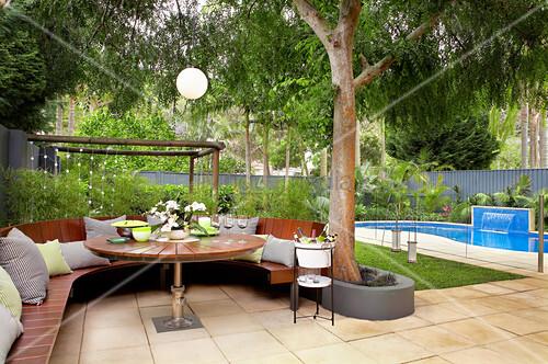 Runde Bank und Tisch auf der Terrasse neben dem Pool