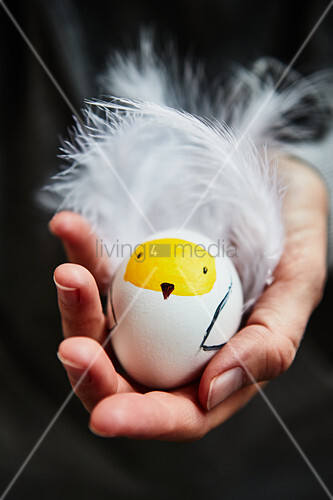 Easter egg with chick motif held in hand