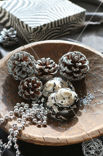 Christmas decorations in natural shades in wooden bowl in front of zebra-patterned box