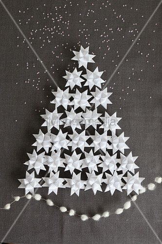 Christmas tree made from 3D origami stars on grey linen fabric