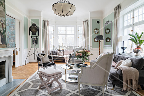 Stylish seating around round table in living room with window bay