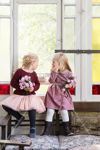 Two girls holding flowers sitting in front of period window with stained-glass elements