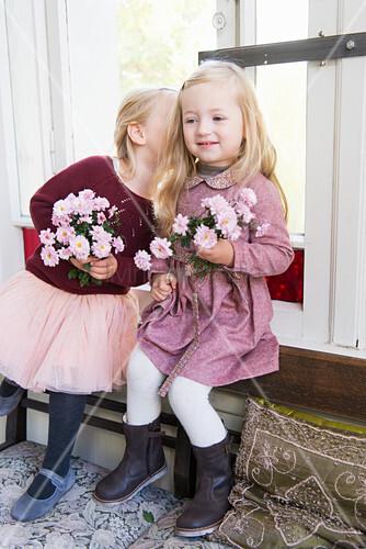 Zwei Mädchen mit Blumen flüstern