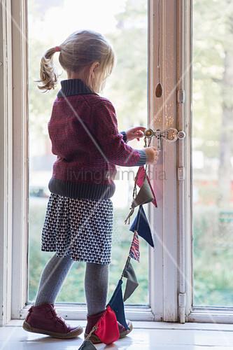 Mädchen hängt Wimpelkette ans Fenster