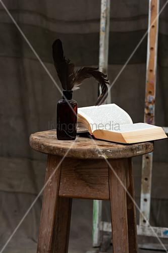 Aufgeschlagenes Buch und Flasche mit Feder auf Holzhocker
