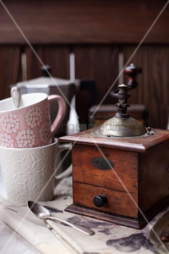 Vintage Kaffeemühle, daneben Kaffeebecher