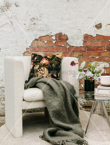 Woollen blanket and floral cushions on armchair against brick wall