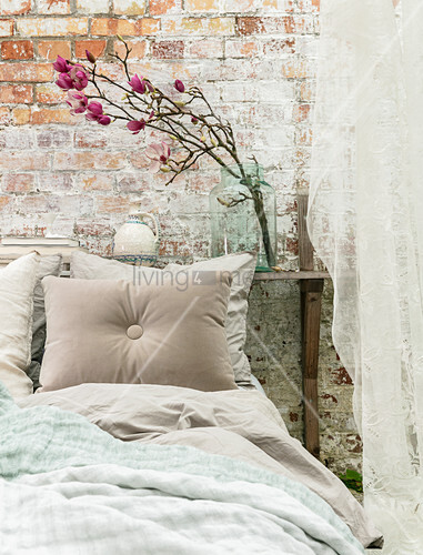 Branch of flowering magnolia on shelf behind bed against brick wall