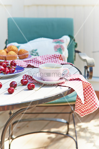 Tasse Kaffee, Kirschen und Muffins auf sommerlichem Gartentisch