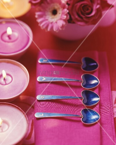 Place setting with heart-shaped spoons and candles