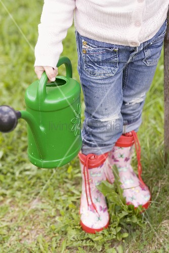 Kind mit Giesskanne im Garten