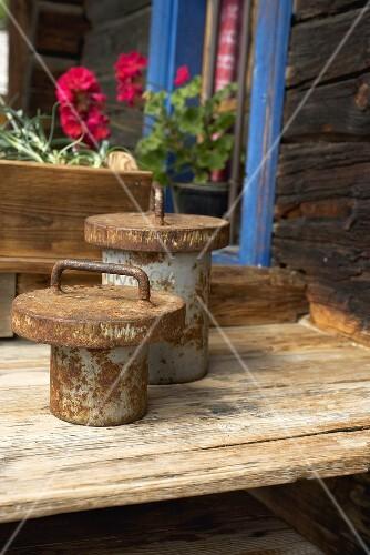 Rostige Gewichte auf Holztisch vor altem Blockhaus