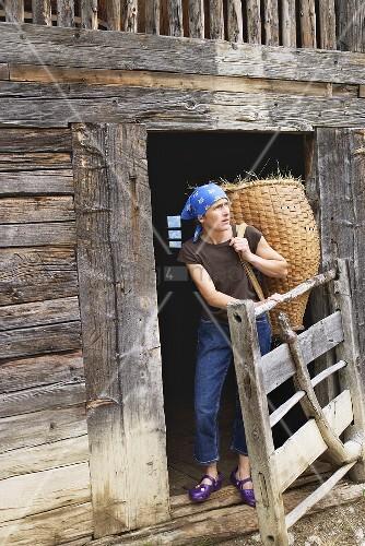 Moderne Bäuerin mit Heukorb auf dem Rücken vor altem Blockhaus
