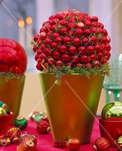weihnachtsdeko aus roten baumkugeln und moos im bertopf bild kaufen living4media. Black Bedroom Furniture Sets. Home Design Ideas