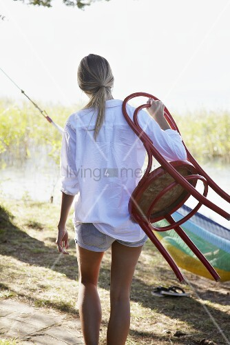 Young woman with a chair by a lake