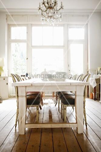Weisses Geschirr auf weissem Holztisch vor hohem Altbau-Fenster