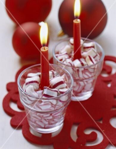 Kerzen in Gläsern mit weiss-roten Bonbons