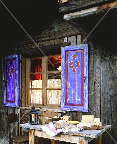 Various French Alpine cheeses outside a wooden chalet