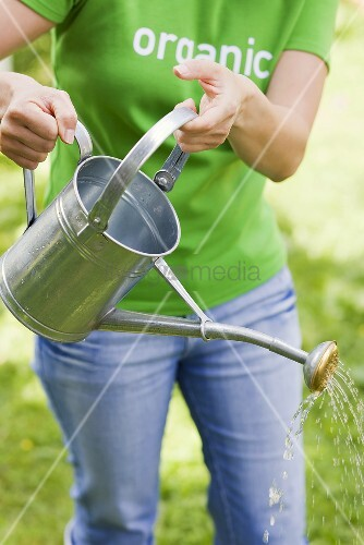 A woman with a watering can in a garden