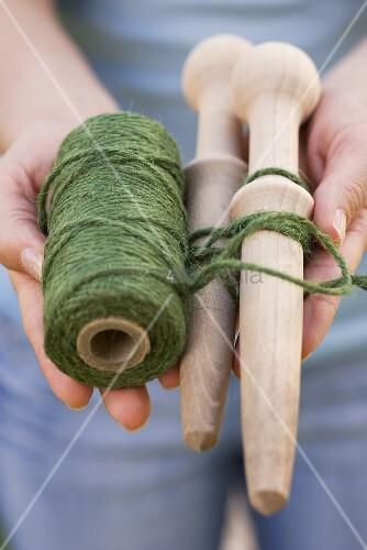 Frau hält Schnur und Holzpfähle