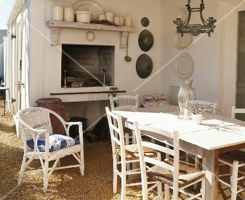 sonnige terrasse mit offenem kamin rustikalem esstisch einfachen binsenst hlen und einem. Black Bedroom Furniture Sets. Home Design Ideas