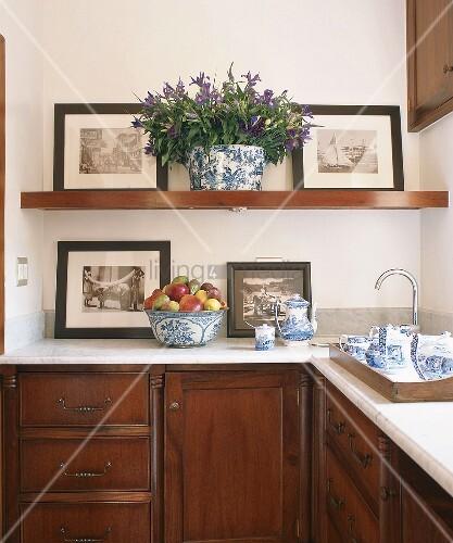 k chenregal mit nostalgischen schwarz weiss fotografien davor teegeschirr in blau weiss auf. Black Bedroom Furniture Sets. Home Design Ideas